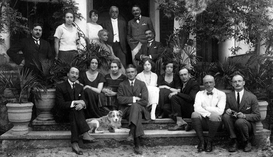 At the Hochepied household, family and friends, Seidikeuy April 1922<br /> left to right, 1st row standing: Mr Langlois, Mlle Jeanne Cua, Ctsse Blanche de Hochepied, Mr Gérard Wissing, Mr Morrin, Inspecteur du Crédit Lyonais.<br /> 2nd row sitting: Ctsse Edmond de Hochepied, Mr M Graillet, Consul Génèral du France à Smyrne<br /> 3rd row sitting: Ctsse Wemy de Hochepied, Mme Langlois, Mme Léouce Guŷs, Ctsse Elise de Hochepied, Mr L Steeneken.<br /> 4th row sitting: M Léouce Guŷs, des Messageries Maritimes; Cte Daniel de Hochepied; Cte Edmond de Hochepied; Mr Tubeuf, du Chemin de fer Smyrne, Cassaba et Prolongement.